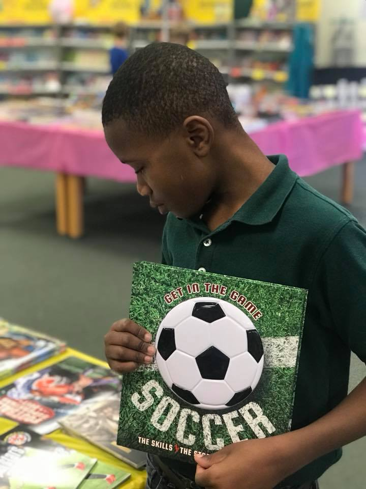 Boy in a green shirt holding a book about soccer